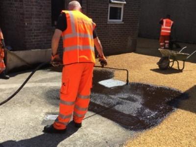 Spraying down hot bitumen on driveway in Somerset